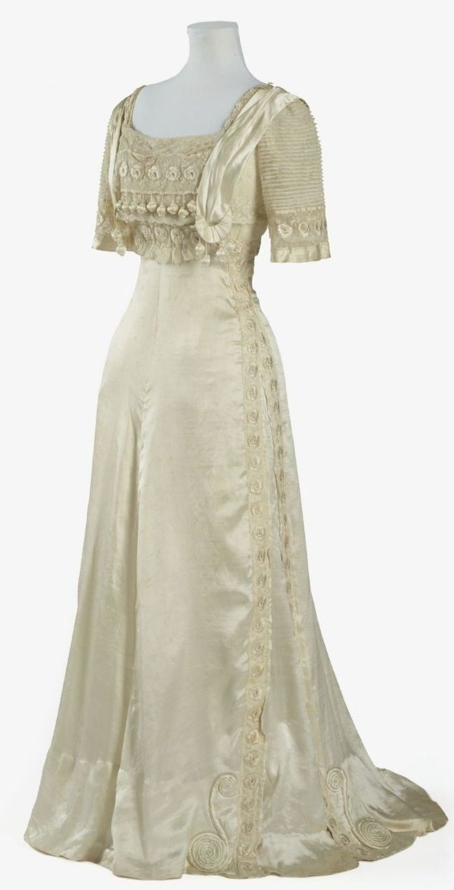 """Evening Dress: ca. 1905-1909, silk satin. """"This dress epitomises the elegant feminine fashions of the well-to-do in the Edwardian period, particularly in its use of soft flowing pale silk, extensive use of lace and net, and in the ornate decoration of the bodice."""""""