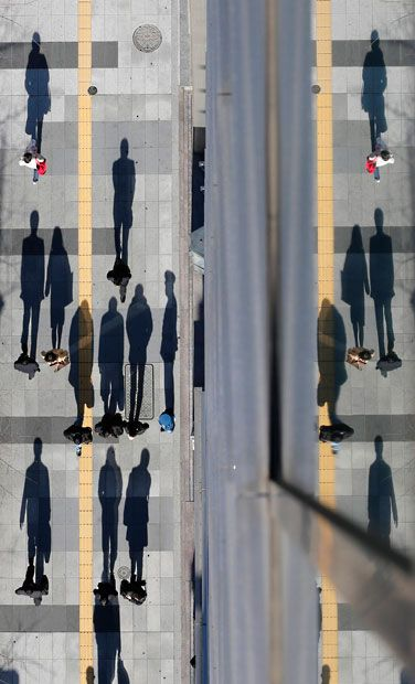 Pedestrians cast shadows on the pavement near the headquarters of the Bank of Japan in Tokyo
