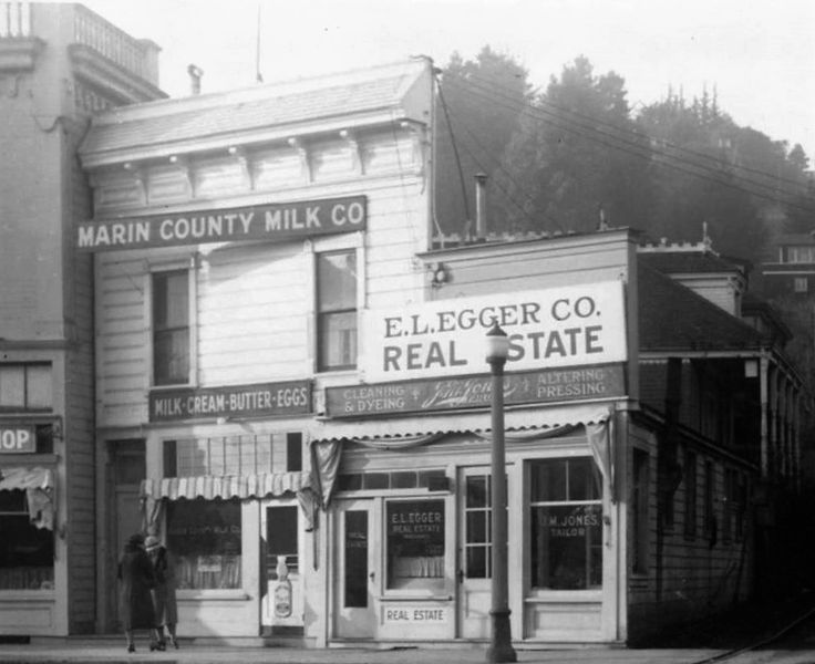 "Shops on Lytton Square, Throckmorton Avenue 1920-24 - One shop says ""Marin County Milk Co"" and ""Milk-Cream-Butter-Eggs"". Another says ""E.L. Egger Co. Real Estate"". Another sign on the same building says ""J.M. Jones Tailors"", ""Cleaning and Dyeing"" and ""Altering and Pressing."" Two women are conversing on the sidewalk outside the milk store. A lamp post is in front of the real estate storefront. Behind the building you can see trees and a house up the hill."