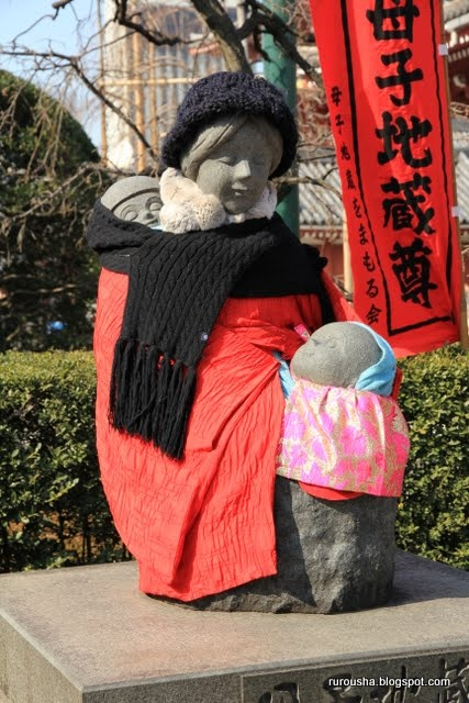 """This statue is at Sensō-ji in Asakusa. It was built """"to comfort the spirits of mothers and children in Manchuria towards the end of World War II"""". The statue is always dressed warmly during winter. Tokyo, Japan"""