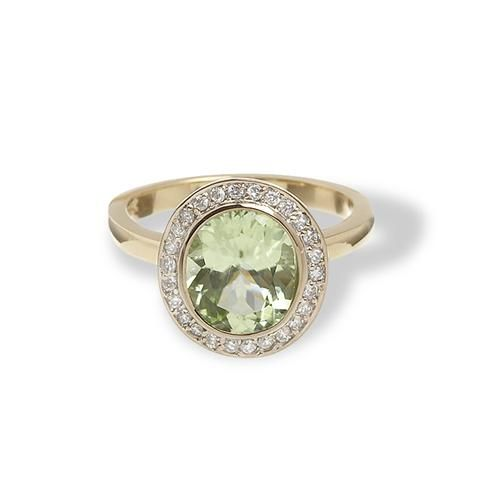Greenwich Collection Oval-Shaped Peridot Ring with Diamonds. This yellow gold ring features a luscious, light green oval-shaped peridot center stone surrounded by a prismatic halo of micropave diamonds. Perfect as an alternative engagement ring or a cocktail ring for evening wear. Made completely from recycled gold and conflict-free diamonds.