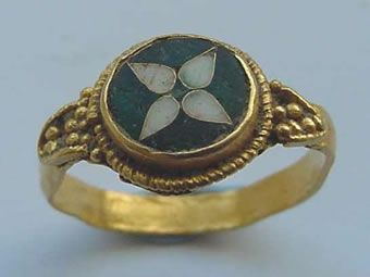 Anglo-Saxon ring, circa tenth century. The ring's center is extremely well made, consisting of fine quality gold wire with green and white enamel. The actual band of the ring is not of the same quality, indicating that it was perhaps made by two different individuals. It was found near Warwick and now belongs to the Warwickshire Museum.