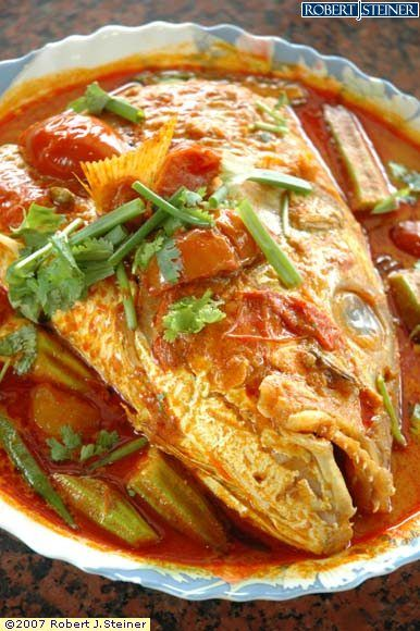 """In Malaysia and Singapore,Fish head curry (Chinese and Indian roots) is a dish where the head of an Ikan Merah (red snapper, literally """"Red fish""""),is semi-stewed in a Kerala-style curry with assorted vegetables such as okra and brinjals and usually served with either rice or bread."""