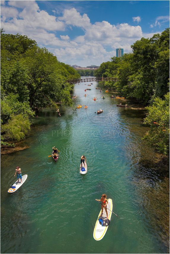 Lady Bird Lake and Zilker Park, both favorites of locals in Austin, Texas provide an endless array of opportunities to enjoy outdoor life. In this picture, kayakers and folks on paddle boards coast through the emerald waters beneath the Austin skyline