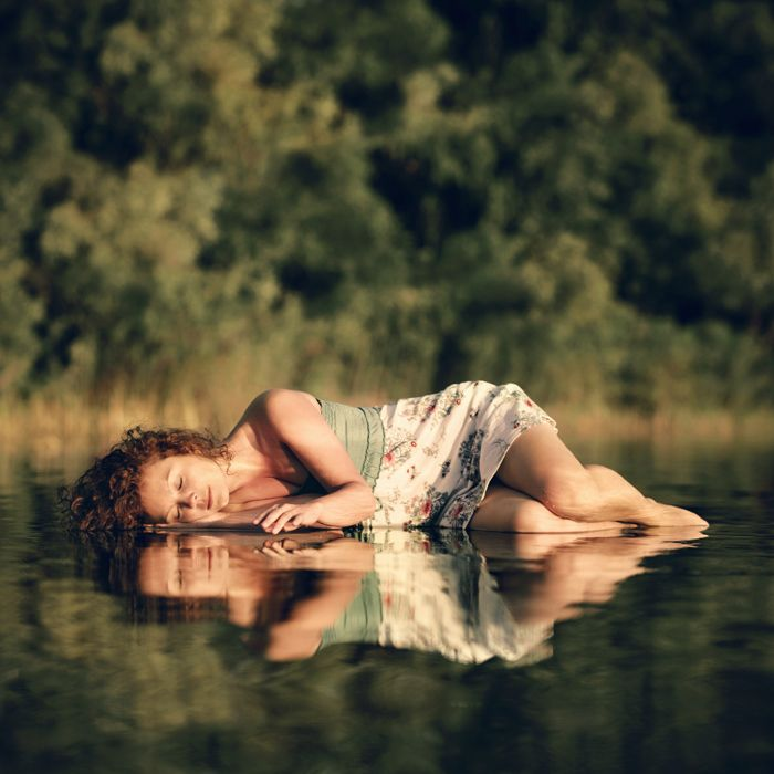 The girl was lying on the chairs, that were under the water, 2-3cm in deep near bank. The water was calm, so reflection is clear) Lightning is the sun setting down the horizon.