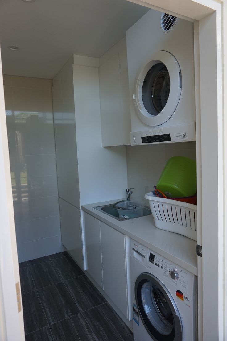 Laundry with front loader under bench, dryer above, sink cabinet, plenty of storage stone bench top
