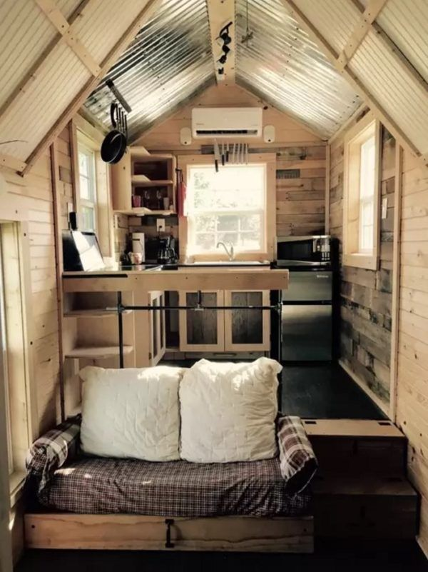 Tiny house interior with raised kitchen and couch.