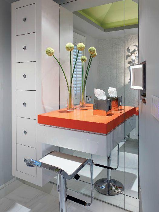 Современный туалетный столик с яркой оранжевой столешницей, простым дизайном и огромным зеркалом.