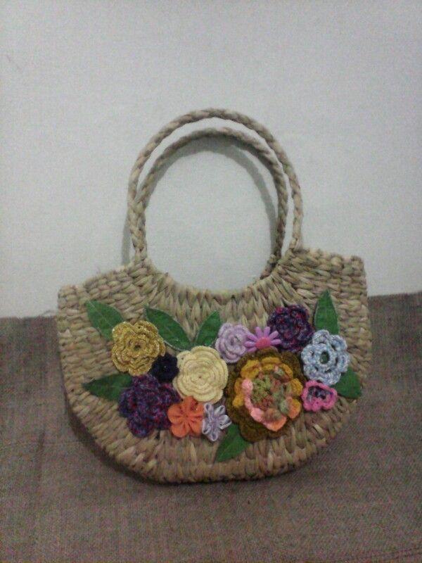 Bolsa de palha artesanal com flores de croche e folhas de tecido