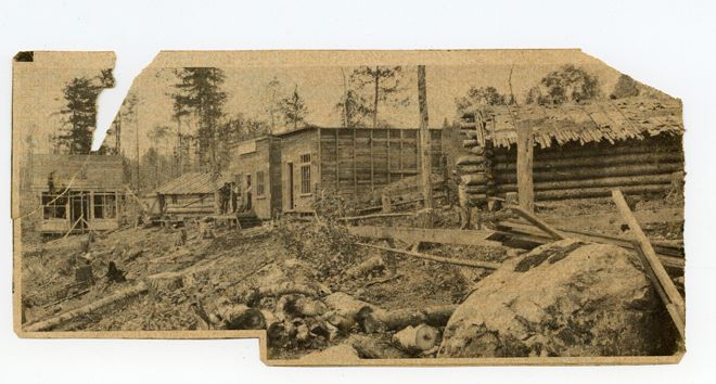 A photograph of five early buildings in Cobalt. There are boulders and tree stumps strewn everywhere.