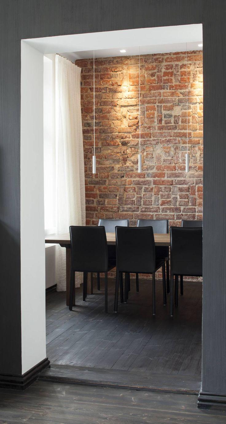 Näkymä olohuoneesta ruokailutilaan. Tiiliseinä otettiin remontissa esiin rappauksen alta. Helsinkiläinen puuseppä Vesa Lempiö on tehnyt ruokapöydän. Valaisimet Halogen Galleriasta, tuolit BoConceptin.