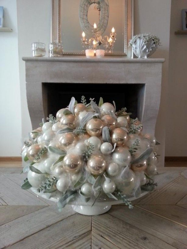 Use pearly Christmas balls in place of roses for this opulent centerpiece, adding soft textures of feather and dusty miller or lambs ear to contrast the shiny finish of the ornaments. (There is a bit of optical illusion going on here warps the perceived size of the arrangement, but the centerpiece is actually on a table, not the floor)