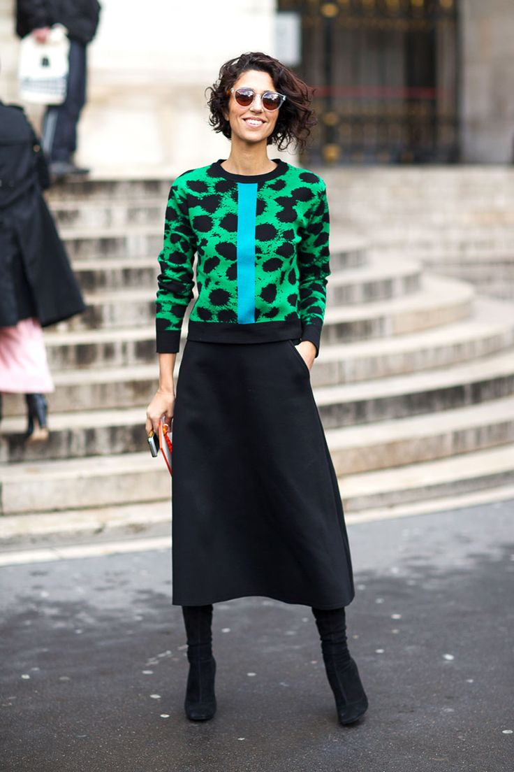 Yasmin Sewell in graphic colourful sweater – green with big black dots and a mint coloured statement stripe, calf length black skirt. Paris Fashion Week, Street style.