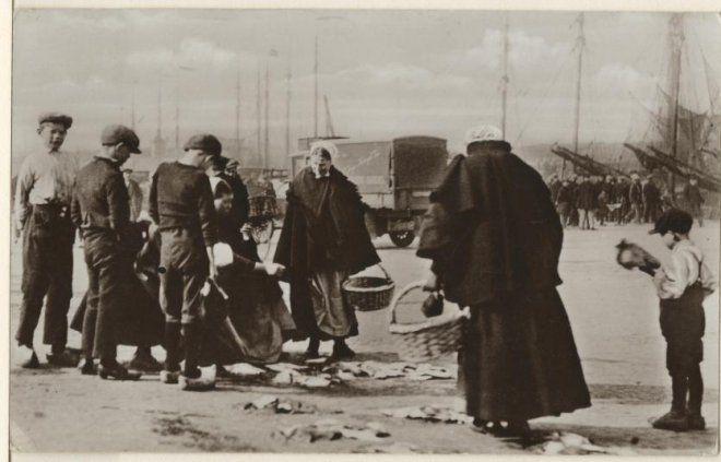 Partijtjes vis op de kade van de eerste haven, Scheveningse vrouwen met vismanden maken een keuze. ca 1930 Roukes & Erhart, NV Luxe Papierwarenhandel v/h, Baarn, nr. 12 #ZuidHolland #Scheveningen