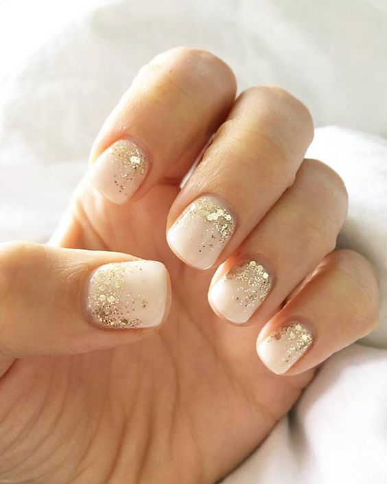white nails with gold sequins on the nail bed