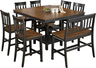 Ashley Owingsville SQ DRM CTR EXT Table and Barstool Set - The rich cottage beauty of the Owingsville dining collection uses a rich medium brown finish on chair seats and table tops contrasting the painted black color of the table base and chair legs to create a stylish two-tone cottage look that is sure to add a warm inviting atmosphere to any dining area.