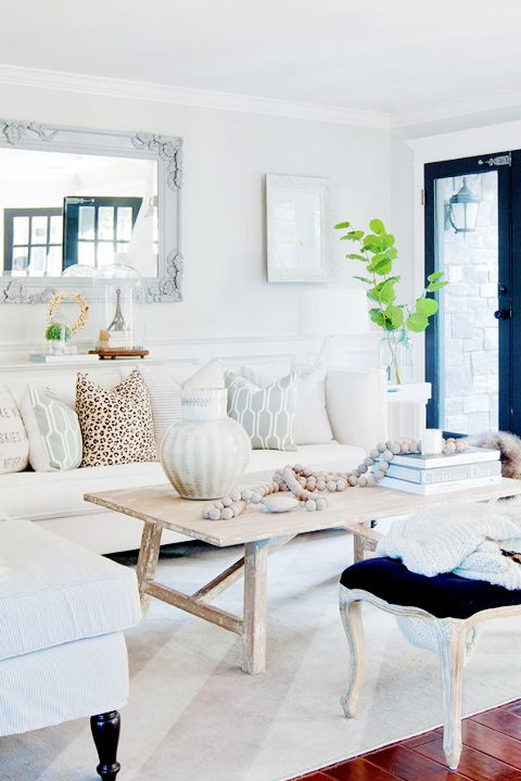 Chic living room features a white sofa covered in gray geometric pillows and a leopard print pillow facing a weathered trestle coffee table and a black French bench.