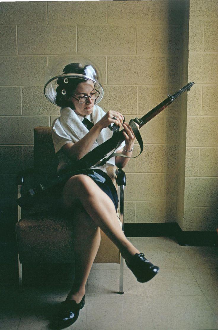 Woman at beauty shop wearing hair rollers, sitting under hair dryer, loading her gun. david alan harvey
