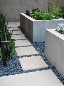 """this is uncolored, sand finished concrete with 4"""" spacing between pads, which are filled with 1/2"""" - 1"""" black beach pebbles."""