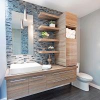 Un ancien bahut-vaisselier en bois massif bénéficie d'une seconde vie dans la salle de bain. Recouvert d'une peinture au latex très lustrée et orné de fines poignées, le voilà recyclé en meuble-lavabo double! Les modules du haut, eux, ont repris du service dans la zone de lavage adjacente. Accentuée de touches de blanc et de matières luisantes, la pièce est tout à fait lumineuse.