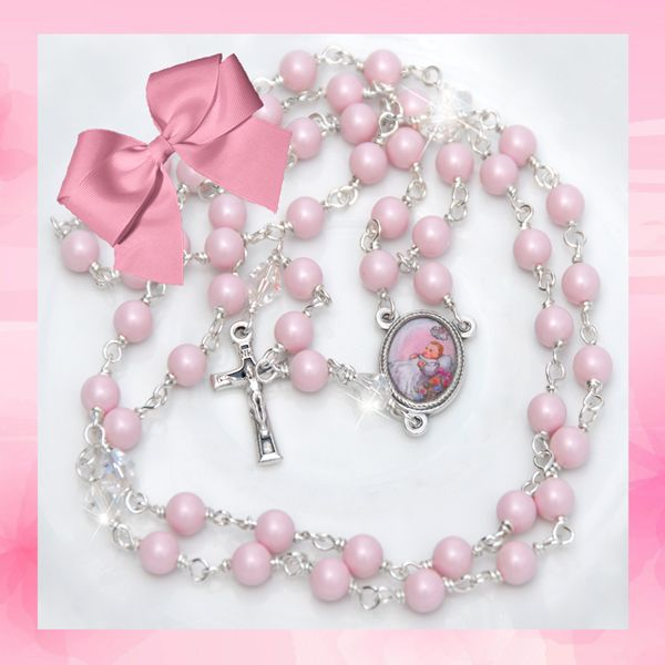 Baby Pink Christening Rosary - A classically beautiful pearl and crystal Christening rosary.  Aves of lustrous 6mm pastel rose Swarovski pearl and Paters of sparkling 6mm clear crystal. The center medal is a silver tone 18mm by 14mm colour depiction of a little girl at her Christening. The crucifix is a beautiful enamelled silver tone design measuring 23mm by 12mm.