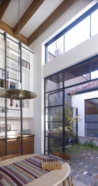 Clerestorey windows sit above the door to the courtyard¬