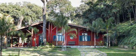 Pousada no meio da mata como um pássaro vermelho, a casa tem fachada simples e uma decoração acolhedora.