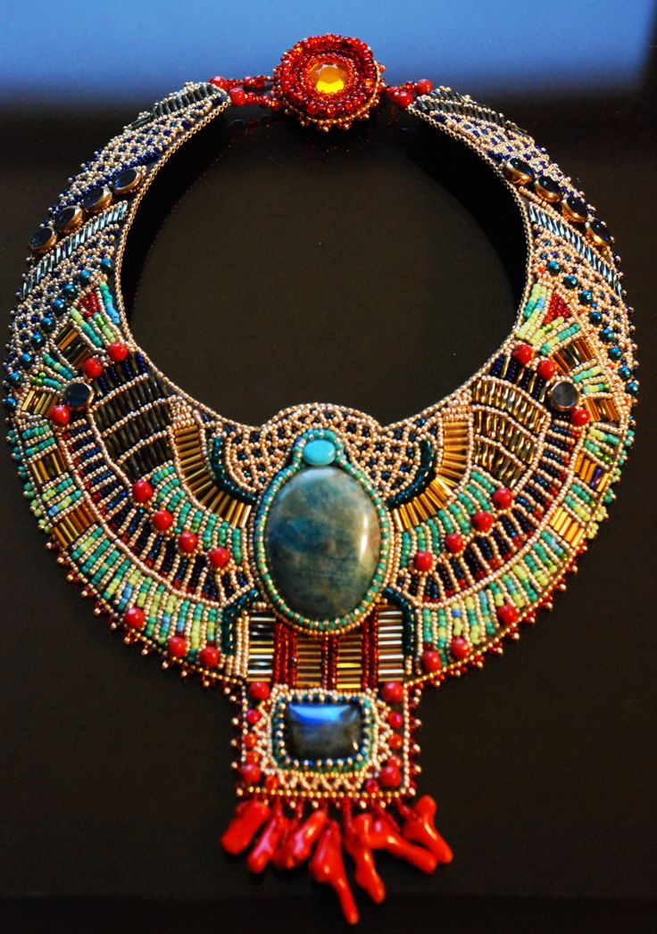 Necklace | Doro Soucy. 'Egyptian Scarab' The scarab in the center is an apatite cabochon in shades of turquoise colors. It is surrounded by Japanese, German and Czech bugle and seed beads, faceted dark red corals, and glass beads. The necklace also features an amazing labradorite cabochon that depending on angle of light reveals gorgeous blues and greens. The fringe is made of dyed red coral branches.