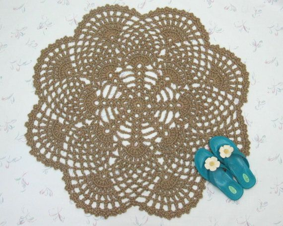 "Here's a handmade crochet jute rug, roughly round, shaped like a flower, or maybe pineapples. I've also seen this type of rug described as mandala rugs, and this would be wonderful for Indian decor. It's about 41"" across at the widest point. Have a look at the textured pattern. It's actually quite like an oversized doily. This is a perfect accent for a kitchen, an entryway, a dorm room, even a boat or a mancave. It would also make for excellent cabin decor, with it's natural, primitive look."
