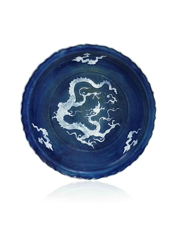 An exceptionally rare foliate rim dish decorated in white slip with relief dragon and clouds on a cobalt-blue glaze, Yuan Dynasty (1279-1368). Photo courtesy Littleton & Hennessy Asian Art Ltd.