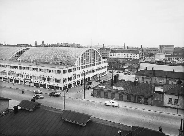 Kampin aluetta Fredrikinkadulta päin kuvattuna vuosina 1938-39. Tennispalatsia ympäröivät puurakennukset Kampintorilla ja taustalla ovat linja-autoasema, Maitokeskus ja Postitalo.Kuva: Helsingin kaupunginmuseo