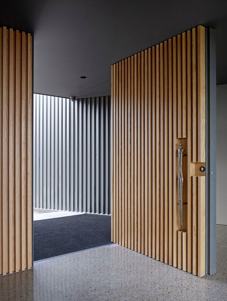 This large pivoting front door covered in light wood slats has a sculptural door handle set into the wood to welcome you into the home.