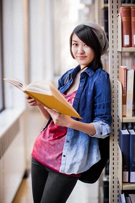 Asian college student studying in the library by aremafoto | Stocksy United