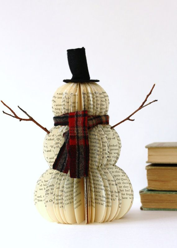 This one... will melt your heart. Its a sweet little snowman made from an old vintage book. A felt handmade stove pipe hat, a cute wool scarf and two stick arms, adorn this little Frosty. Hes also coated with a dusting of clear snow glitter. Details:  Approximately 91/2tall, 5 1/2wide (not including arms), 8 1/2 wide with arms.    Stores and ships flat. This is a custom made order for 1 vintage book snowman. Just like snowflakes, each snowman varies slightly. The hat and shape will look…