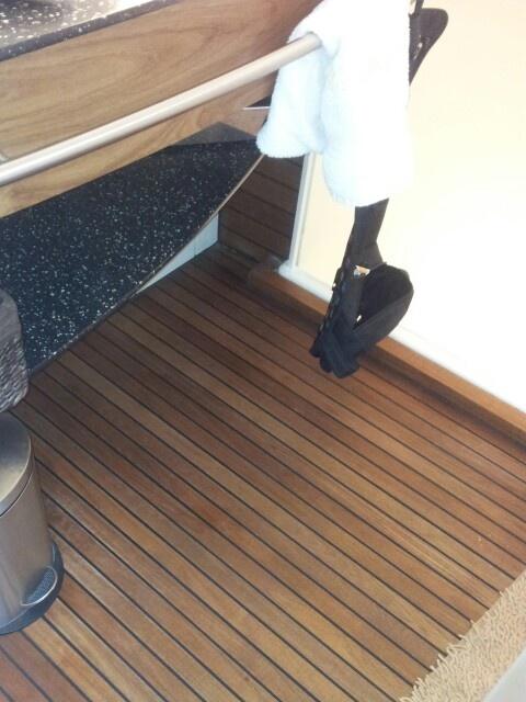Leuke vloer voor in badkamer. Houten klik-laminaat, met rubberen tussenstukken. Lijkt wat op boot vloeren.