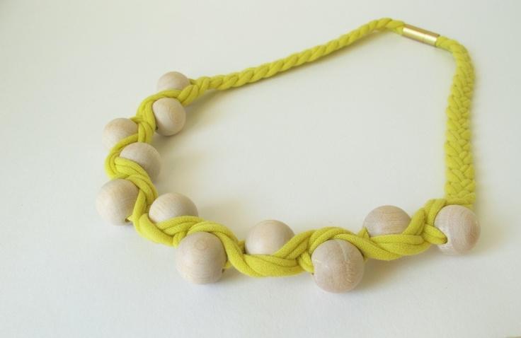 neongelbe jerseybänder verflochten mit naturfarbenen holzperlen zu einer leichten kette, die sich mit mit mattgoldenen magneten schliesst.