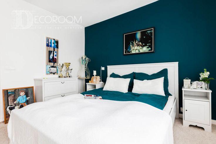Ścianę za łóżkiem w sypialni pomalowano na odważny - turkusowy kolor. Nawet tak wydawałoby się niewielka zmiana dodaje pomieszczeniu indywidualnego charakteru. Na podłodze położono kremową wykładzinę, która współgra z bielą mebli. Sypialnię wyróżniają ciekawe dodatki.