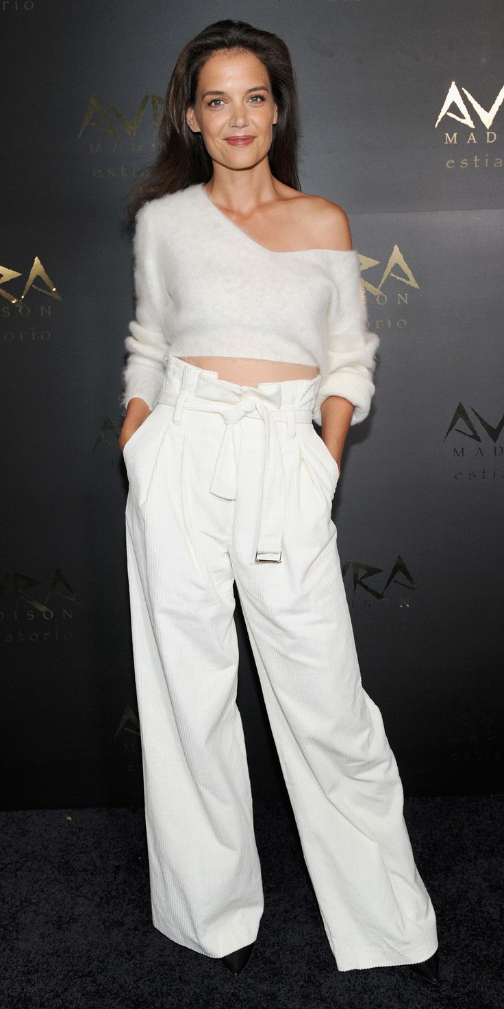 In perhaps Katie Holmes's most contemporary-chic look yet, the brunette beauty gave the one-shoulder shrug at the Avra Madison grand opening party in a fuzzy slouchy cropped knit with high-waist wide-leg white pants.