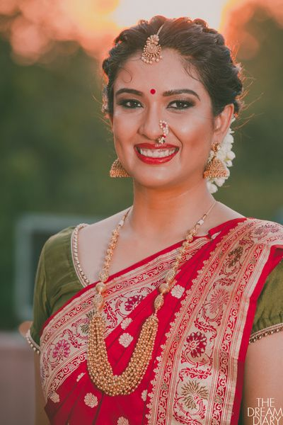 Marathi Bride in Traditional Red Saree with a Green Blouse, Gold Rani Haar, Jhumkis, Maangtikka, and Nath, with Jasmine Flowers