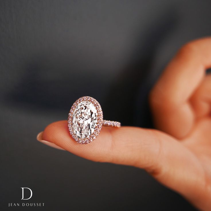 EVA PINK, exclusively from the Jean Dousset Diamonds La Vie En Rose® collection, is a handcrafted engagement ring shown with an Oval Cut diamond in 18K Rose Gold. The La Vie En Rose® collection features rare, Fancy pink diamonds that are imported from the premiere Argyle Diamond Mine in Western Australia. #OvalCut #PinkDiamonds #EngagementRing #RoseGold #pink #pinkdiamondring  #ovaldiamondring #ovalring #haloring #diamond #diamonds #jewelry #ring #rings #ringinspiration #rose #jeandousset