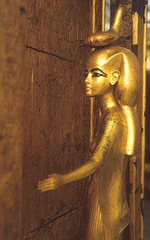 This goddess is Selket, who wears her emblem, a scorpion, on her head. The figure is highly naturalistic, with her arms outstretched to protect the chest and its contents, and her head is inclined slightly to one side. Her face and figure are modeled after Ankhesenamun, Tutankhamen's wife/sister.