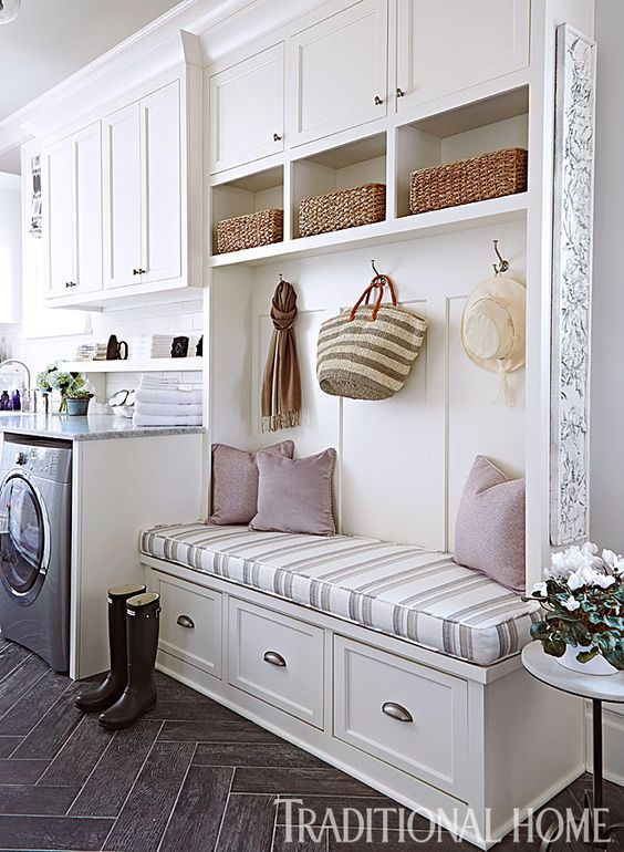 Lovely Showhouse Kitchen   Traditional Home - Laundry & Mudroom by Kim Zimmer. The laundry and mudroom are high-functioning spaces that include the house's back entrance, so Kim Zimmer divided the long, narrow space into zones based on usages. Near the door is a built-in bench with storage drawers, cubbies, and hooks for coats, hats, and bags. A durable wood-look tile floor from Cerdomus stands up to daily traffic in this 24x8-foot room.: