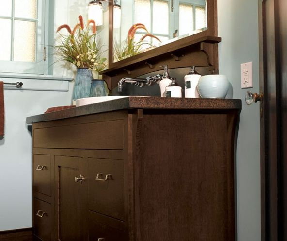 Make Photo Gallery  charming paint color with traditional crown moulding and a rich vanity cabinet like this one by Omega Cabinetry for a fun and inviting bathroom design
