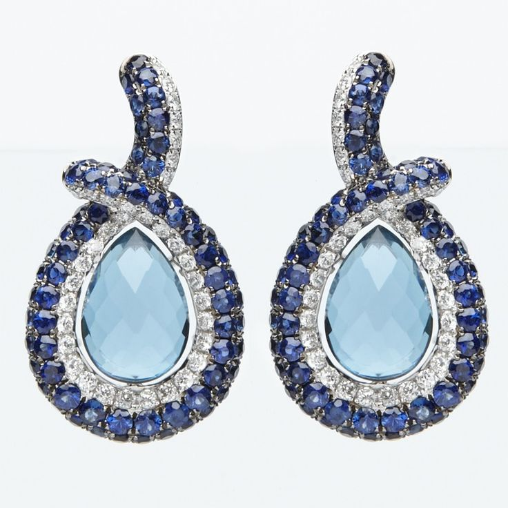 Graceful in design, these drop earrings feature richly  hue London Blue Topaz with round diamonds and sapphires that cascade along the stud hoops and frame the centre gemstones, all set in 18k white gold.