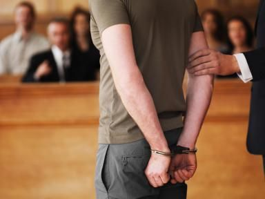 Handcuffed man standing in courtroom - Chris Ryan/OJO Images/Getty Images