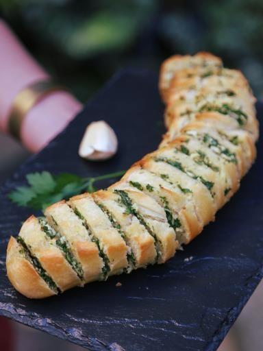 Baguette beurre à l'ail : 1 petite baguette précuite, 100 g de beurre salé, 4 gousses d'ail, 1 bouquet persil plat. Couper la baguette en tranche, sans aller jusqu'au bout (les tranches de pain doivent être jointes sur 2 cm environ). Hacher les gousses d'ail avec le persil. Mélanger le beurre mou, l'ail et le persil, pour former une pâte homogène. Tartiner ce mélange, entre les tranches de pain (des 2 côtés des tranches). Mettre au four à 180°C.