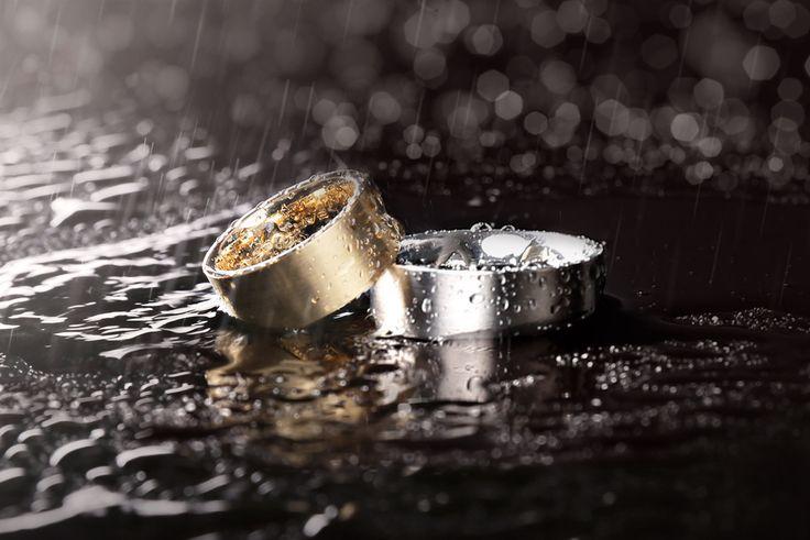 Trouwringen - Gold & Steel. Een paar gematteerde brede trouwringen waarvan de damesring vervaardigd is van geelgoud en de herenring van staal.   [Fotografie: Lenka Stangler Fotografie]