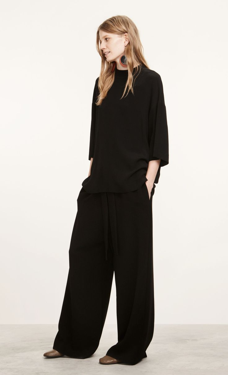 Made out of black viscose crepe, this loose fit tunic has dropped sleeves, a straight cut to the below-hip hemline and a long slit at the back seam below a set of collar ribbons that can be tied together at the nape of the neck.