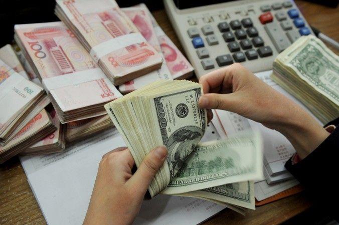 Um caixa do banco conta maços de notas de dólar americano e notas chinesas de 100 yuan em Hefei, China (STR/AFP/Getty Images)