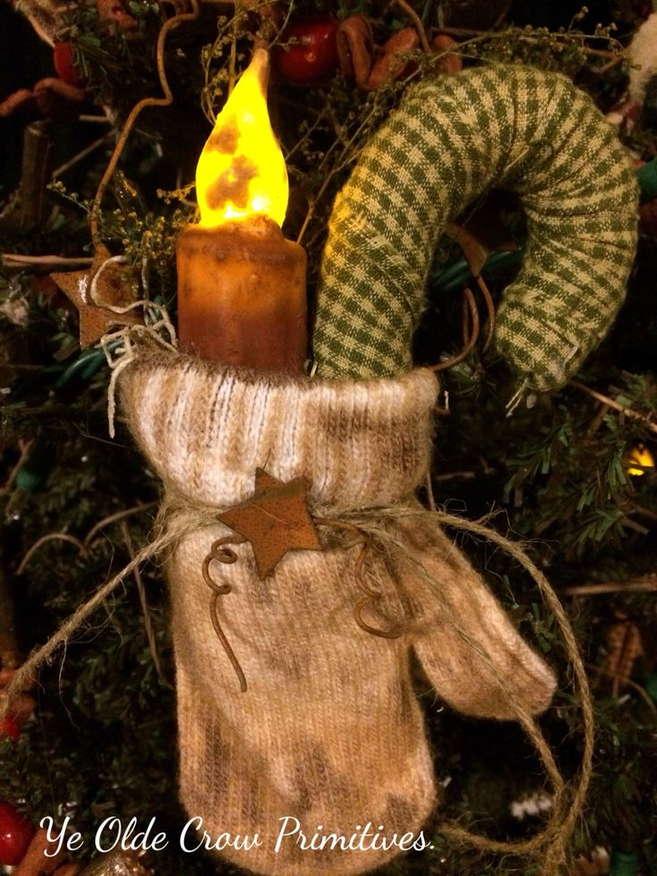 Little primitive mitten with LED candle stick candy cane and rusty tin that I've made for a tree or wreath by ye Olde crow primitives